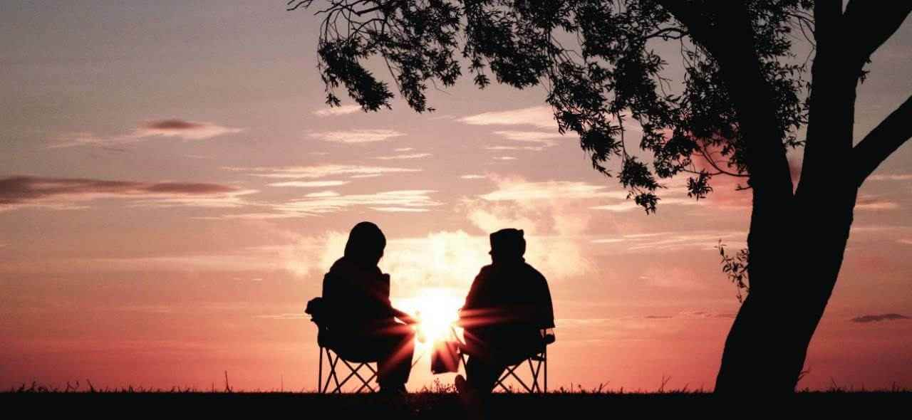 two people sitting in chairs, talking, under a tree at sunset